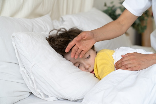 La madre preoccupata controlla la temperatura del ragazzo malato con il bambino malato alla mano con influenza o malattia covid dorme a letto