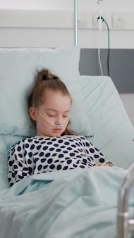 Madre preoccupata seduta accanto alla piccola figlia che prega mentre dorme dopo un intervento chirurgico di malattia