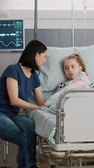 Madre preoccupata seduta accanto alla figlia malata durante l'esame di malattia nel reparto ospedaliero per discutere del trattamento sanitario. bambino ricoverato con tubo nasale di ossigeno che subisce un intervento chirurgico di recupero