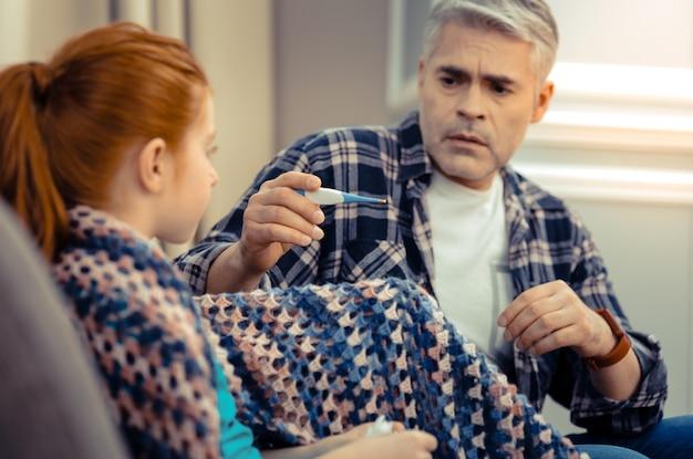 Genitore preoccupato. triste uomo ansioso che tiene in mano un termometro mentre controlla la temperatura corporea di sua figlia