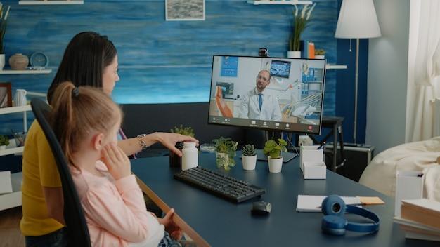 Genitore preoccupato che parla con il dentista in videochiamata del bambino