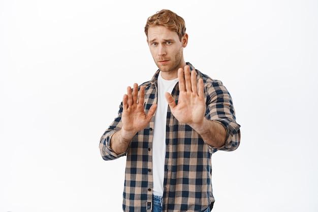 Uomo rosso preoccupato che chiede di mantenere le distanze, alzando le mani in segno di divieto, nessun gesto, bloccando o rifiutando una cattiva offerta, in piedi sul muro bianco