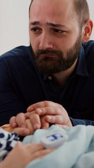 Padre triste preoccupato che piange accanto alla figlia malata in attesa di cure sanitarie durante la consultazione medica di recupero nel reparto ospedaliero. bambino che dorme in convalescenza dopo un intervento chirurgico per malattia