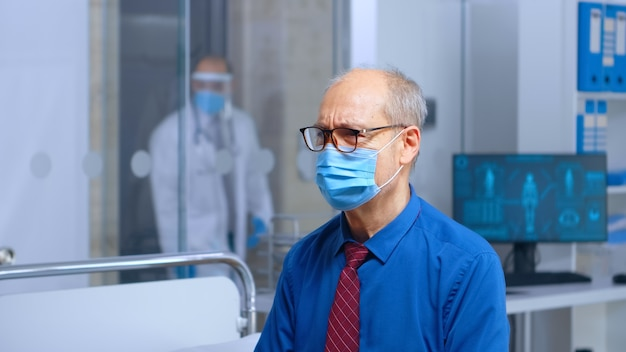 Paziente anziano preoccupato con una maschera alla consultazione del medico, seduto sul letto d'ospedale, in attesa dei risultati di covid-19. struttura clinica sanitaria sanitaria privata. scatto a mano libera al rallentatore