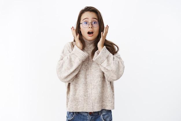 Donna carina preoccupata e scioccata che mostra empatia e tremava mentre reagiva a incredibili notizie terribili bocca aperta e alzando le sopracciglia con gli occhi a sorpresa tenendosi per mano vicino al viso impresso sul muro grigio.