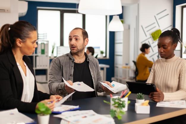 Preoccupato per l'avvio di un team diversificato che discute dei risultati finanziari, discute seduti alla scrivania in ufficio, pianificando la prossima strategia tenendo tablet per la ricerca di soluzioni