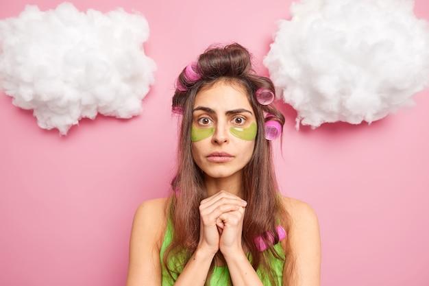 La casalinga sorpresa e preoccupata fa l'acconciatura riccia con i rulli sottoposti a procedure di bellezza che tiene le mani unite in pose contro il muro rosa