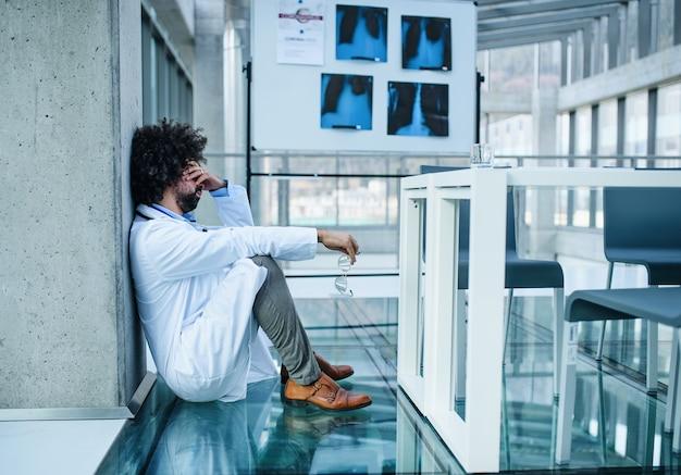 Medico preoccupato e stanco in ospedale, concetto di virus corona. copia spazio.