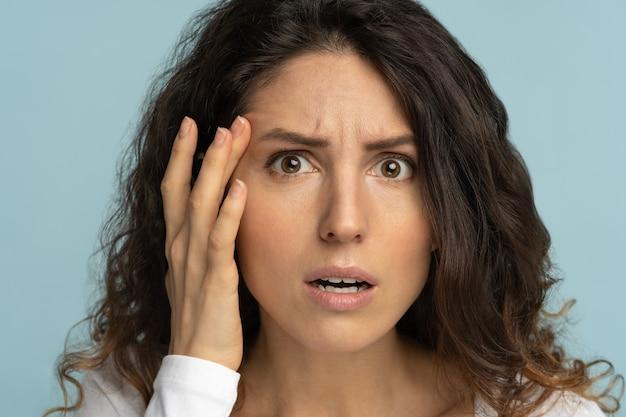 La donna preoccupata ha segni di invecchiamento della pelle, controllando le zampe di gallina disturbate dalle rughe sul viso