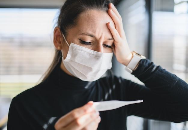 Donna preoccupata dolorante con termometro e maschere facciali in casa, concetto di virus corona.
