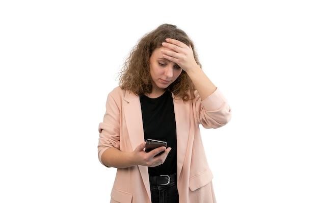 La donna preoccupata mette la sua mano alla testa mentre guarda il suo smartphone isolato