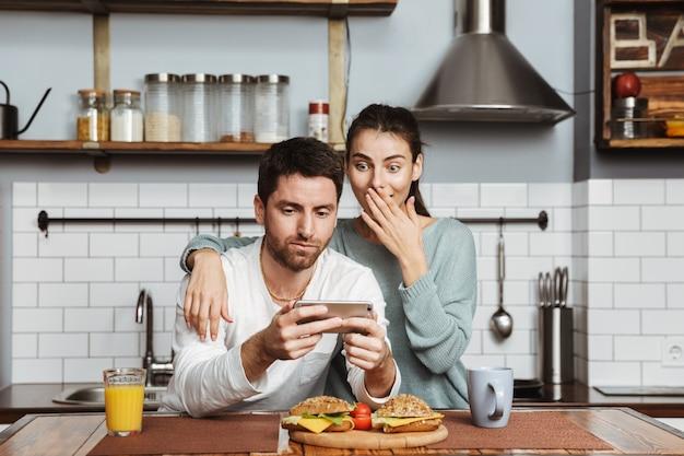 Preoccupato giovane coppia seduta in cucina durante la colazione a casa, guardando il telefono cellulare