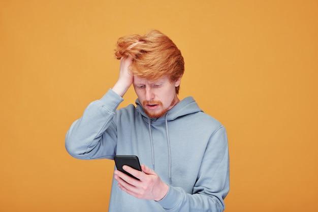 Giovane preoccupato in abbigliamento casual che tocca la testa durante la lettura di notizie online sullo schermo dello smartphone contro il muro giallo