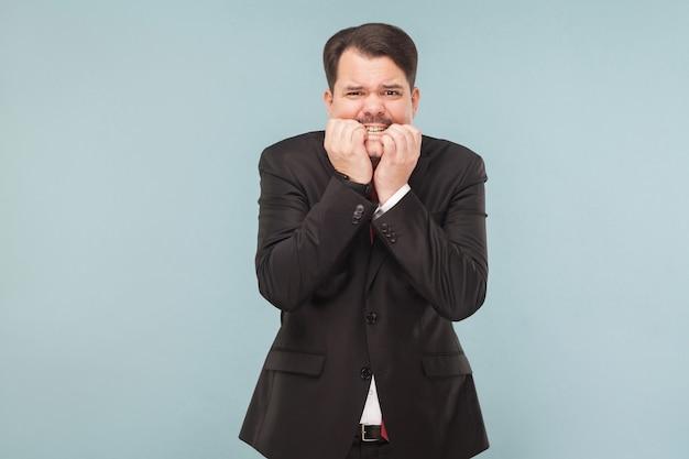 L'uomo d'affari preoccupato si morde le unghie per l'eccitazione