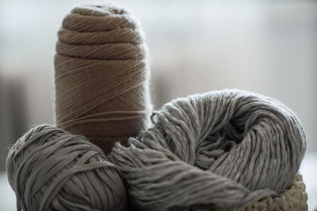 Un cestino intrecciato con filo bianco e grigio per ferri da maglia e ferri da maglia. maglioni bianchi e filati per maglieria primo piano. inverno