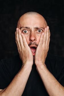 Wow. orrore sulla sua faccia. shock, paura. con la bocca aperta. ritratto di un uomo in una maglietta nera su sfondo nero, coprendosi il viso con le mani. le emozioni umane, il concetto di espressione facciale.