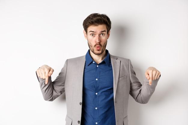 Wow guarda in basso. ragazzo eccitato di affari in vestito che indica la pubblicità inferiore delle dita e sguardo stupito, in piedi su sfondo bianco.