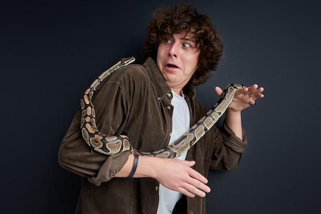 Wow. il maschio reagisce emotivamente al serpente che striscia sul suo corpo, scioccato. muro nero isolato