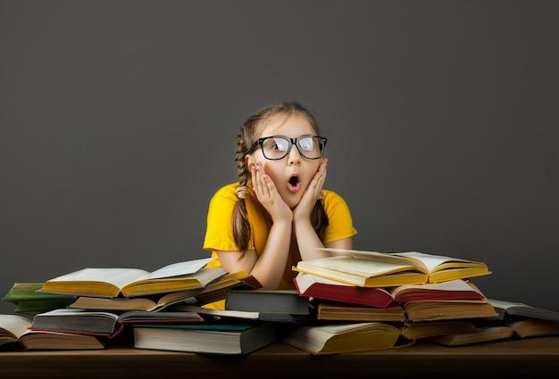 Wow. ritratto della bambina della scuola che si tiene per mano sulla testa