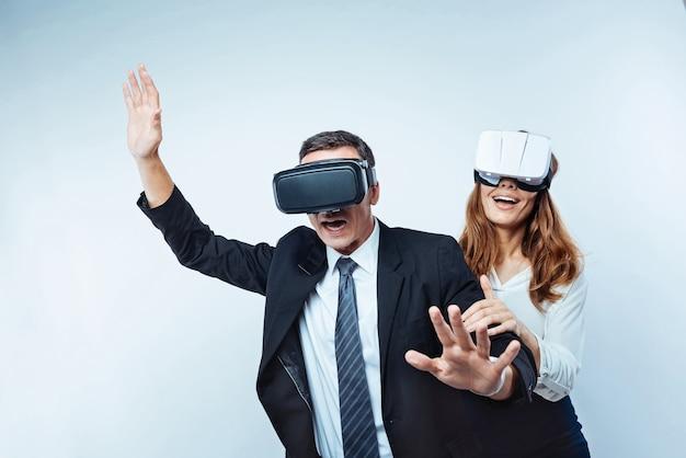 Wow. gli uomini d'affari rilassati non possono mantenere le proprie emozioni dentro e gesticolare mentre provano occhiali per realtà virtuale 3d e ricaricano le batterie dopo aver lavorato sodo.