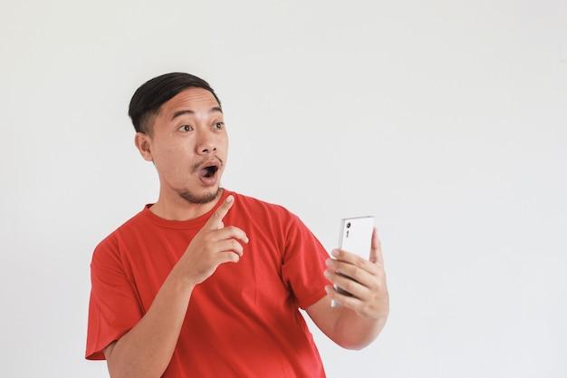 Wow e shock face espressione di un uomo asiatico che indossa una maglietta rossa con il dito indice che punta allo spazio vuoto mentre usa lo smartphone