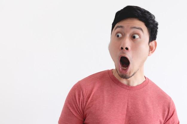 Wow e volto scioccato dell'uomo divertente isolato sul muro bianco