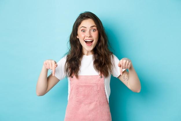 Wow così fantastico. eccitata ragazza carina che racconta grandi notizie, sorride stupita e punta il dito verso il basso, mostra pubblicità interessante, dà consigli, consiglia di dare un'occhiata al promo.