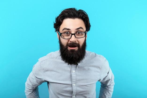 Wow! uomo sorpreso con la bocca aperta, ragazzo scioccato con gli occhiali, sul muro blu