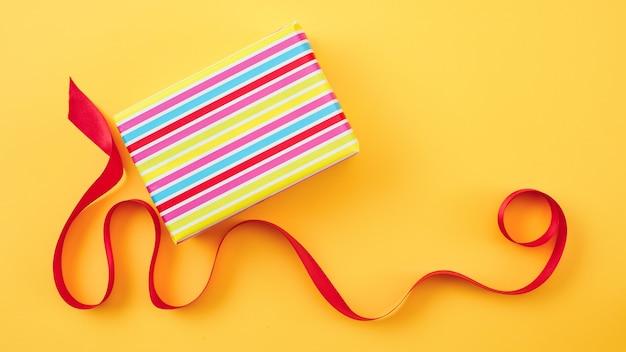 Confezione regalo avvolta e nastro rosso su sfondo di carta gialla, vista dall'alto