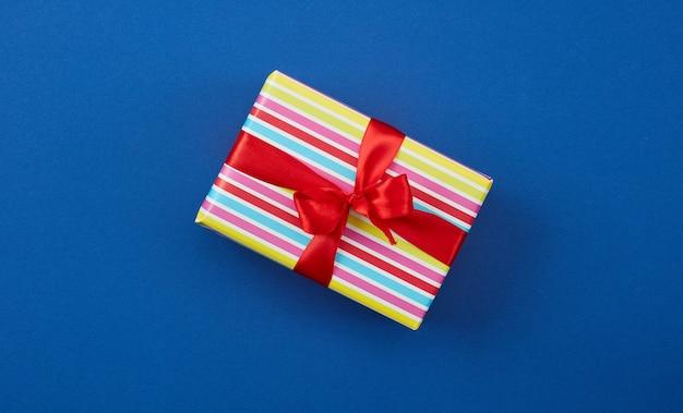 Confezione regalo incartata con nastro rosso su sfondo blu, vista dall'alto