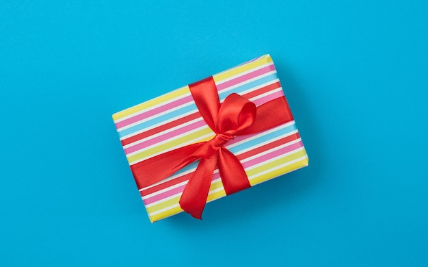 Confezione regalo incartata con fiocco in nastro rosso su sfondo di carta blu, vista dall'alto