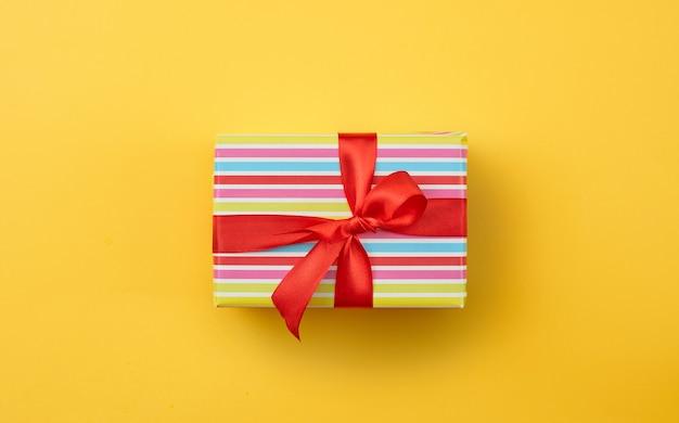 Confezione regalo incartata con fiocco in nastro rosso su sfondo di carta gialla, vista dall'alto