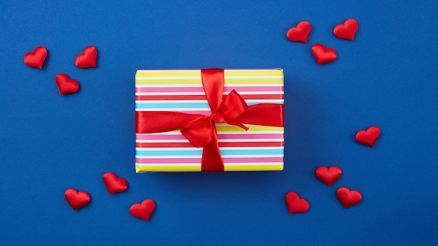 Confezione regalo incartata con nastro rosso e cuori su sfondo blu, vista dall'alto