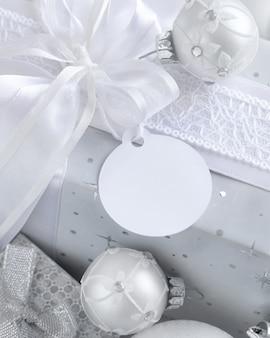 Regalo avvolto con un fiocco bianco e un'etichetta regalo di carta rotonda su un tavolo bianco con decorazioni natalizie bianche e argento da vicino. composizione invernale con carta etichetta vuota, mockup, spazio copia