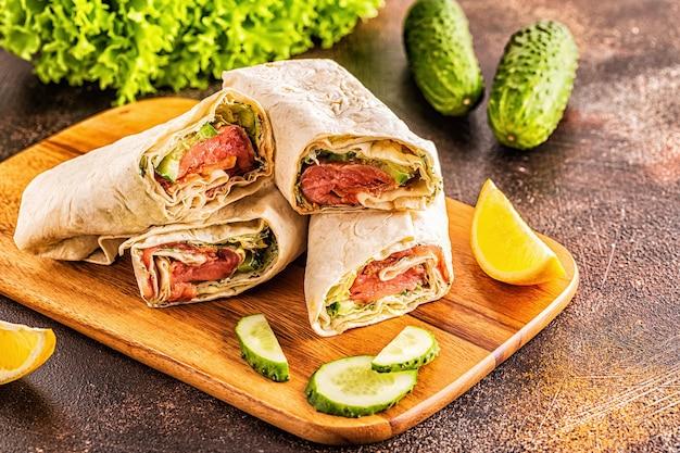 Sandwich avvolto con salmone, lattuga, cetriolo e crema di formaggio, messa a fuoco selettiva.