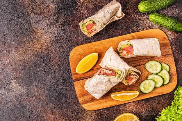 Sandwich avvolto con salmone, lattuga, cetriolo e crema di formaggio, vista dall'alto.