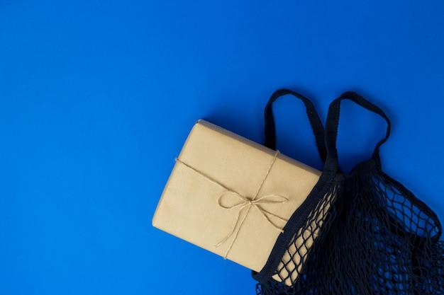 Avvolgere un pacchetto di carta artigianale marrone con canapa e borse della spesa riutilizzabili