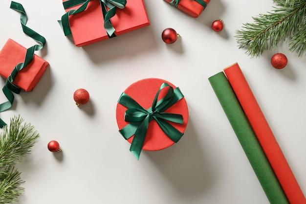 Avvolgere i regali di natale in carta rossa e verde su grigio.