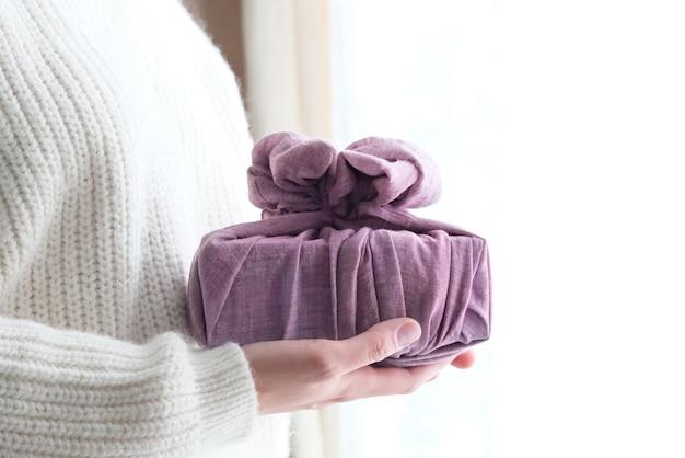 Confezionamento di regali in tessuto per natale in stile furoshiki. concetto ecologico. fai da te