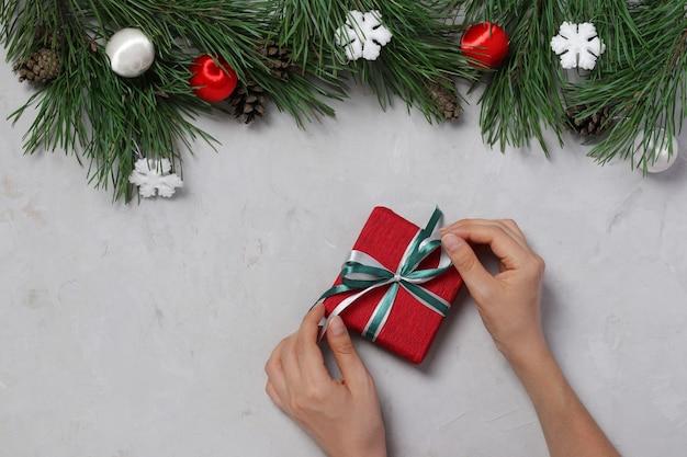 Incartando un regalo di capodanno una donna lega un nastro. sfondo grigio. biglietto di auguri di natale. santo stefano. vista dall'alto