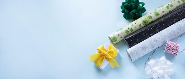 Fiocchi di carta da imballaggio e nastro pronti per il confezionamento di regali su sfondo azzurro banner web con spazio per il testo