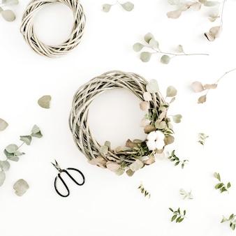 Cornice ghirlanda con batuffoli di cotone e ramo di eucalipto su sfondo bianco. disposizione piatta, vista dall'alto