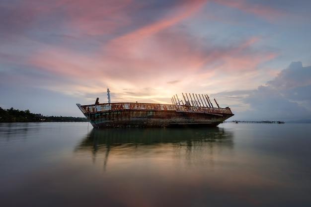 La barca demolita ha abbandonato il supporto sulla spiaggia o ha naufragato fuori dalla costa della tailandia