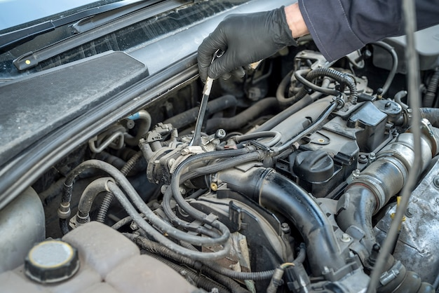 Chiave inglese e strumento di riparazione auto in mano al meccanico per il servizio in garage. riparazione automobilistica