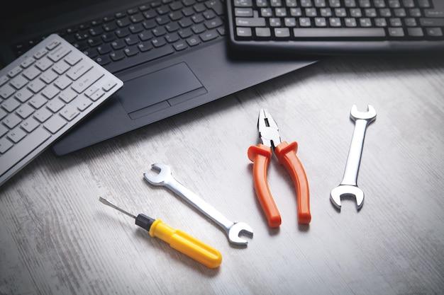 Chiavi, pinze e cacciaviti con laptop e tastiera del computer. servizio informatico. supporto