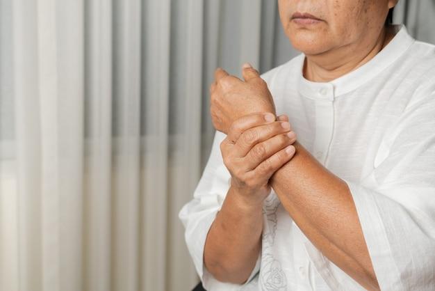Dolore al polso della donna anziana, problema sanitario del concetto senior