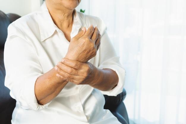 Dolore alla mano del polso della donna anziana, problema sanitario del concetto senior