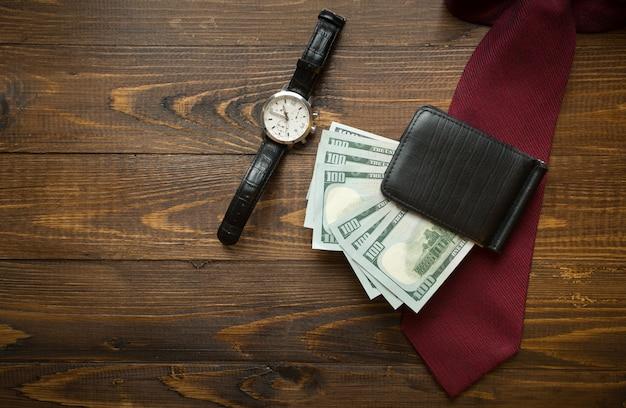 Orologi da polso, soldi in borsa e cravatta rossa su fondo di legno scuro