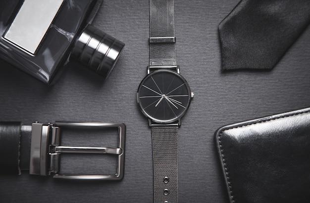 Orologio da polso, profumo, cintura, cravatta, portafoglio sulla tavola nera