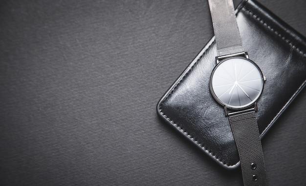 Orologio da polso e portafoglio su sfondo nero.
